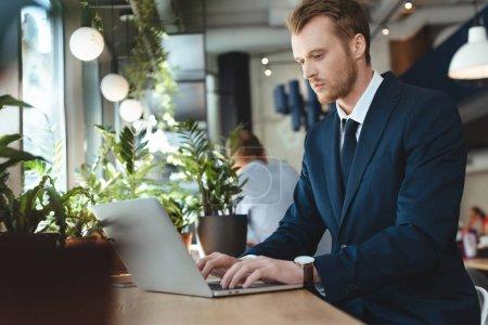 Photo pour Vue latérale de l'homme d'affaires concentré en utilisant un ordinateur portable à la table dans le café - image libre de droit