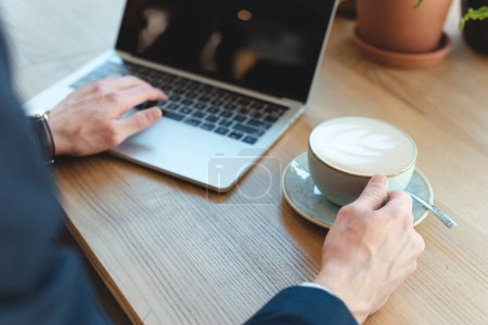 cropped shot of businessman with cup of coffee working on laptop with blank screen in cafe