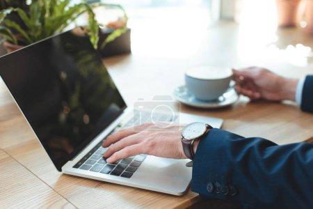Photo pour Plan recadré de l'homme d'affaires avec tasse de café travaillant sur ordinateur portable avec écran blanc dans le café - image libre de droit