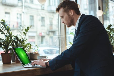 side view of concentrated businessman remote working on laptop at table with cup of coffee in restaurant