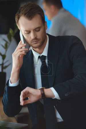 portrait of confident businessman checking time during conversation on smartphone in cafe