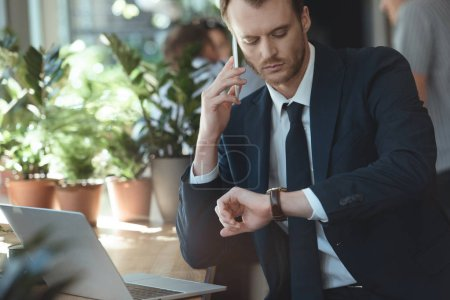 portrait of pensive businessman checking time during conversation on smartphone in cafe
