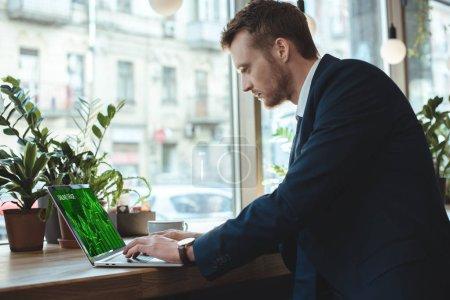 Photo pour Vue latérale du concentré homme d'affaires travaillant sur ordinateur portable avec le lettrage de commerce en ligne sur écran à table par tasse de café au restaurant - image libre de droit