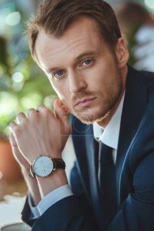 Photo pour Portrait d'homme d'affaires avec montre de poignet en regardant la caméra dans le café-restaurant - image libre de droit