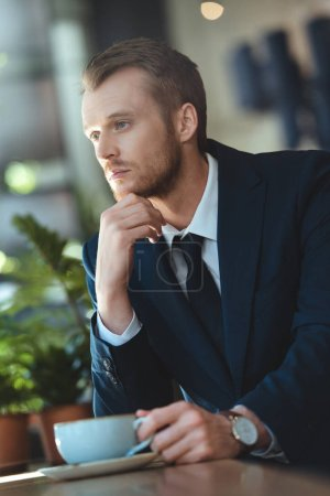 Photo pour Portrait de songeur homme d'affaires en costume avec la tasse de café ayant pause café au café - image libre de droit