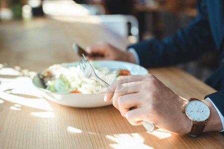 cropped shot of businessman at table with served lunch in restaurant