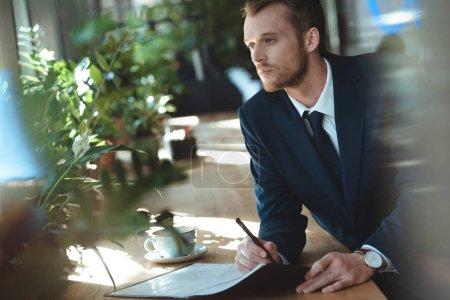 empresario pensativo mirando hacia otro lado mientras hace papeleo en la mesa con una taza de café en el restaurante