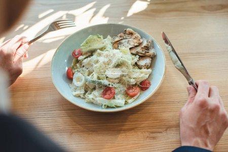 vue partielle de l'homme d'affaires et salade servi pour le déjeuner sur la table dans le restaurant