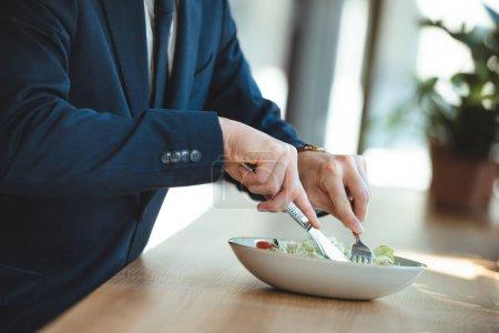 Photo pour Vue partielle de l'homme d'affaires à table avec un déjeuner servi au restaurant - image libre de droit