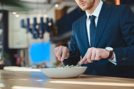 partial view of businessman at table with served lunch in restaurant