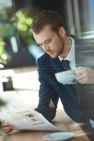 businessman with cup of coffee reading newspaper during coffee break in cafe