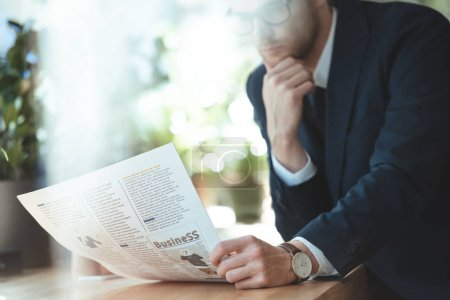 partial view of businessman in eyeglasses reading newspaper during in cafe