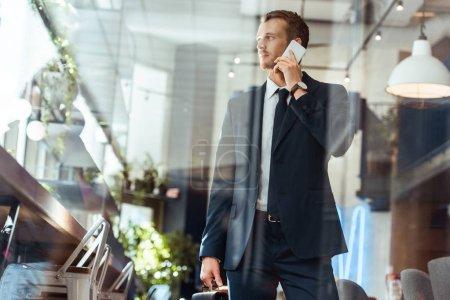 Photo pour Homme d'affaires élégant avec valise parlant sur smartphone dans un café - image libre de droit