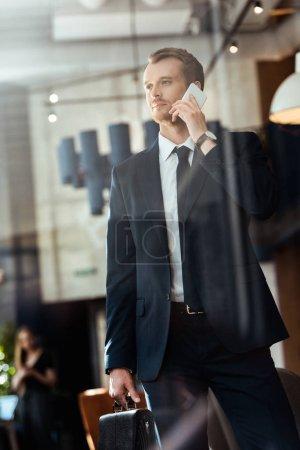 Photo pour Homme d'affaires élégant avec valise parler sur smartphone dans café - image libre de droit
