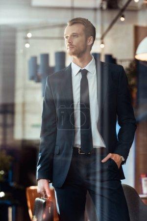 Foto de Retrato del empresario pensativo con maleta mirando lejos en restaurante - Imagen libre de derechos