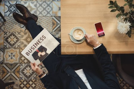 overhead view of businessman with newspaper sitting at table with cup of coffee and smartphone in cafe