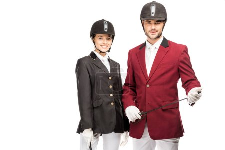 attractive young equestrians in uniform and helmets looking at camera isolated on white