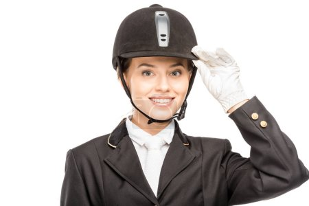close-up portrait of smiling young horsewoman in safety helmet looking at camera isolated on white