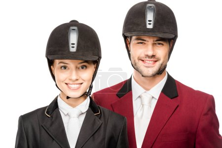 close-up portrait of smiling young equestrians in uniform and helmets looking at camera isolated on white