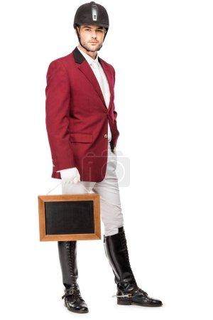 Foto de Atractivo caballero joven en uniforme manteniendo la pizarra en blanco y mirando a cámara aislada en blanco - Imagen libre de derechos