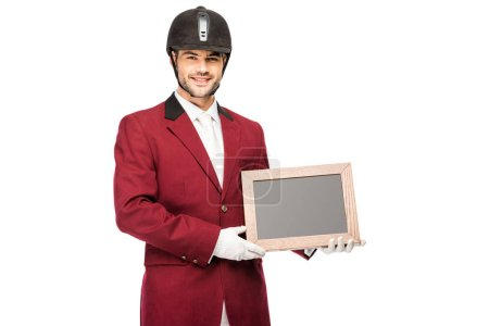 happy young horseman in uniform holding blank chalkboard and looking at camera isolated on white