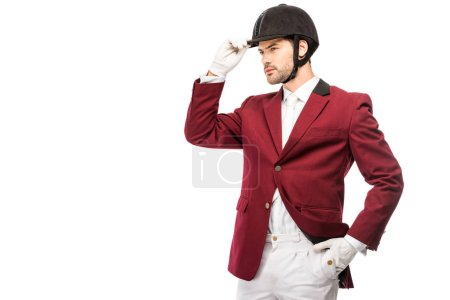 attractive young horseman in uniform and helmet looking away isolated on white