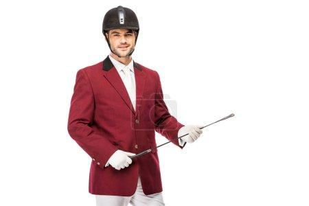 souriante jeune cavalier en uniforme retenir le bâton de cavalier et regardant la caméra isolé sur blanc