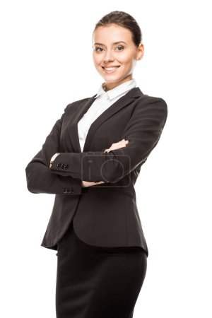 happy young businesswoman in suit looking at camera with crossed arms isolated on white