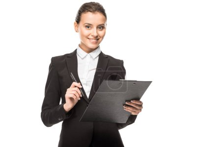 smiling young businesswoman in suit with clipboard looking at camera isolated on white