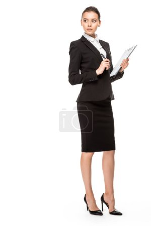 Photo for Beautiful young businesswoman in suit with clipboard looking away isolated on white - Royalty Free Image