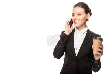 Foto de Sonriente joven empresaria con la taza de papel de café hablando por teléfono, aislado en blanco - Imagen libre de derechos