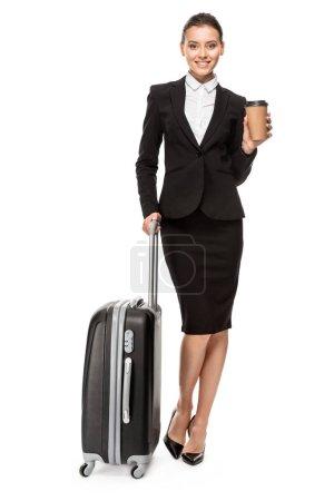 Foto de Feliz empresaria joven en traje con equipaje y papel taza de café mirando a cámara aislada en blanco - Imagen libre de derechos