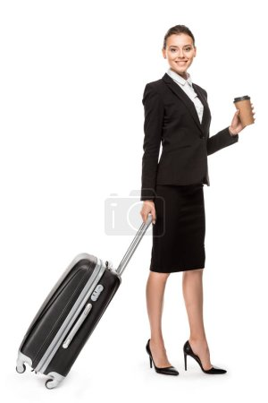 beautiful young businesswoman in suit with luggage and paper cup of coffee looking at camera isolated on white