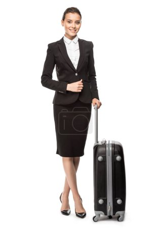 beautiful young businesswoman in suit with luggage looking at camera isolated on white