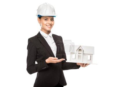 Foto de Toma recortada de sonriente joven mujer arquitecto sosteniendo el modelo de casa miniatura aislada en blanco - Imagen libre de derechos