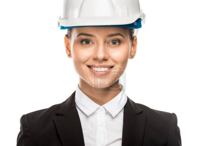 close-up shot of smiling young female architect in helmet and suit isolated on white