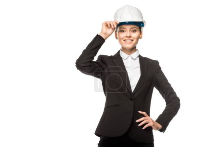 happy young female architect in helmet and suit looking at camera isolated on white