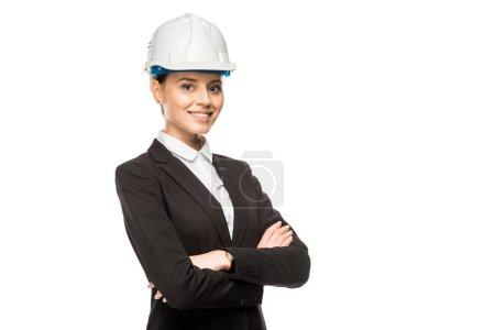 Photo pour Belle jeune femme architecte dans le casque et le costume en regardant la caméra avec les bras croisés isolés sur blanc - image libre de droit