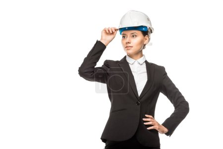 confident young female architect in helmet and suit looking away isolated on white