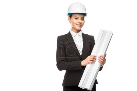 happy young female architect in helmet and suit holding blueprints and looking at camera isolated on white