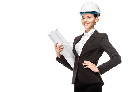 beautiful young female architect in helmet and suit holding blueprints and looking at camera isolated on white