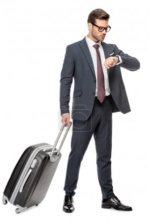 handsome young businessman with luggage looking at wrist watch isolated on white