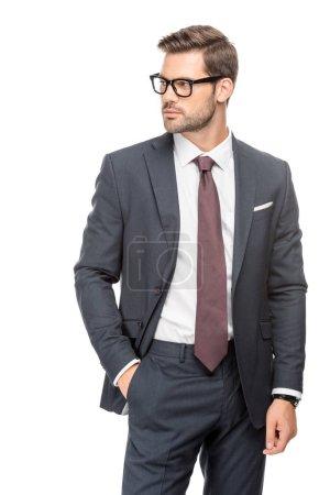 Photo pour Séduisante jeune homme d'affaires en costume et lunettes de vue et à la recherche de suite isolé sur blanc - image libre de droit