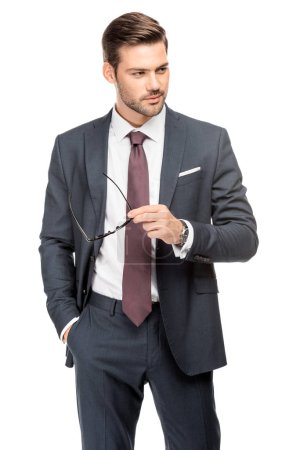 Photo pour Séduisante jeune homme d'affaires en costume tenue lunettes et regarder loin isolé sur blanc - image libre de droit