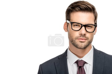 portrait of handsome young businessman in eyeglasses looking at camera isolated on white