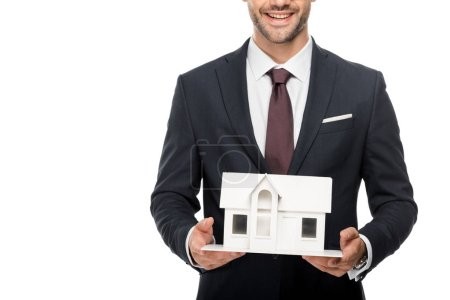 partial view of young male architect in formal suit showing miniature house isolated on white