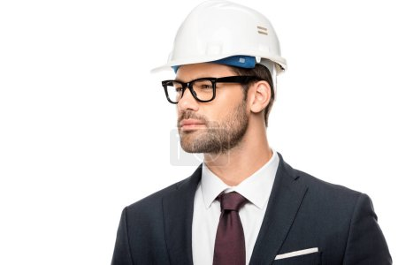 confident young male architect in eyeglasses and hard hat looking away isolated on white