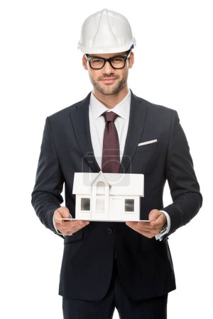 confident young male architect in hard hat showing miniature house isolated on white