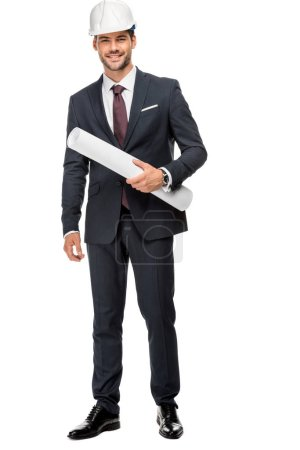 cheerful young male architect in hard hat and jacket holding blueprints isolated on white