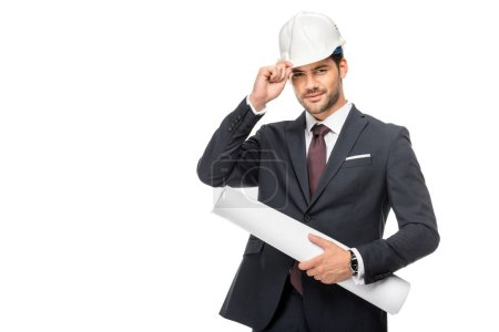 happy young male architect in suit holding blueprints and adjusting hard hat isolated on white